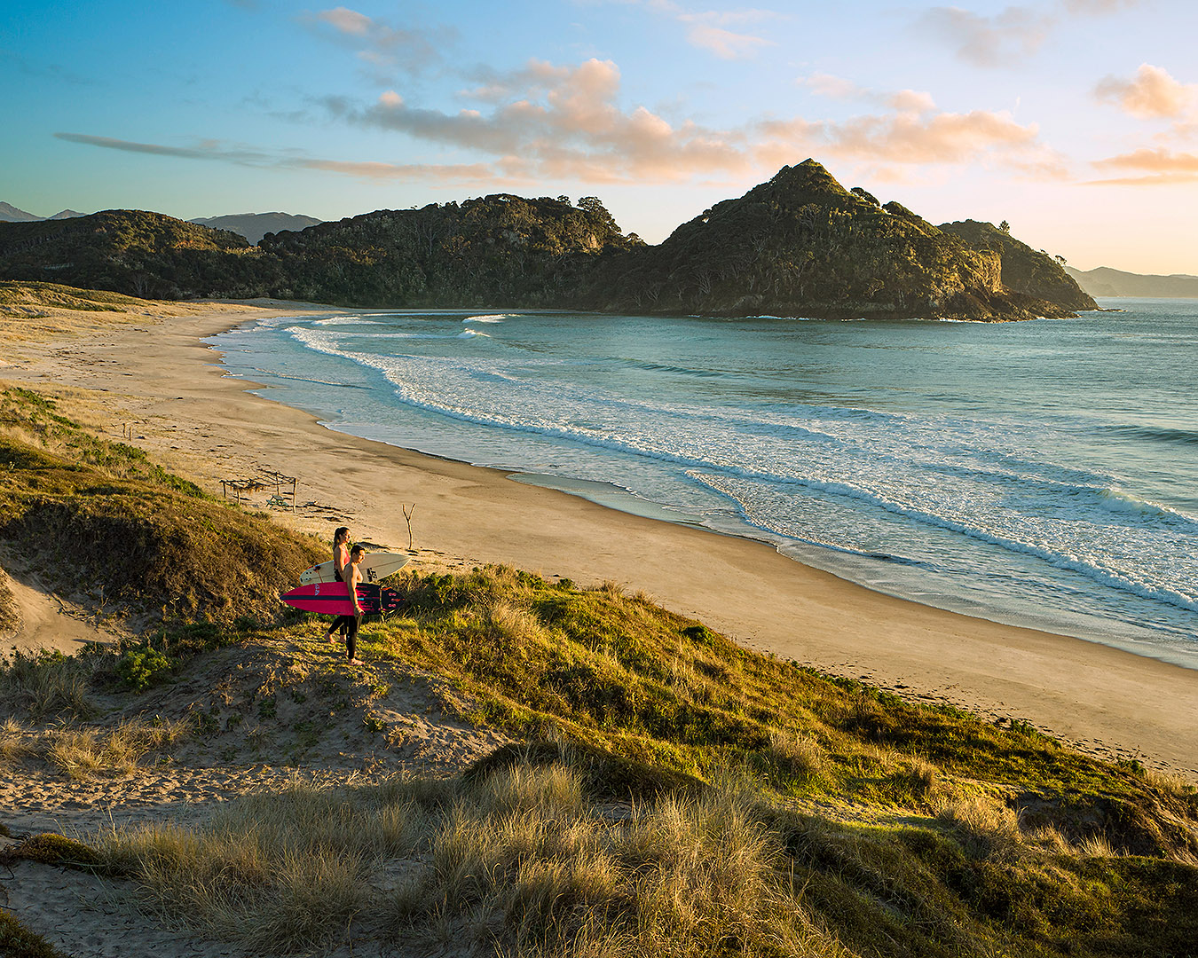 Surfers look out at Medlands Beach on Great Barrier Island.