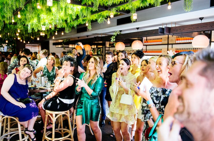 A crowd watching the Melbourne Cup on the rooftop at Hadiqa.