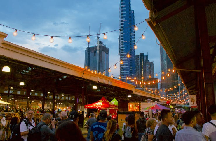 A shot of the Queen Victoria Market at night with the CBD in the background.