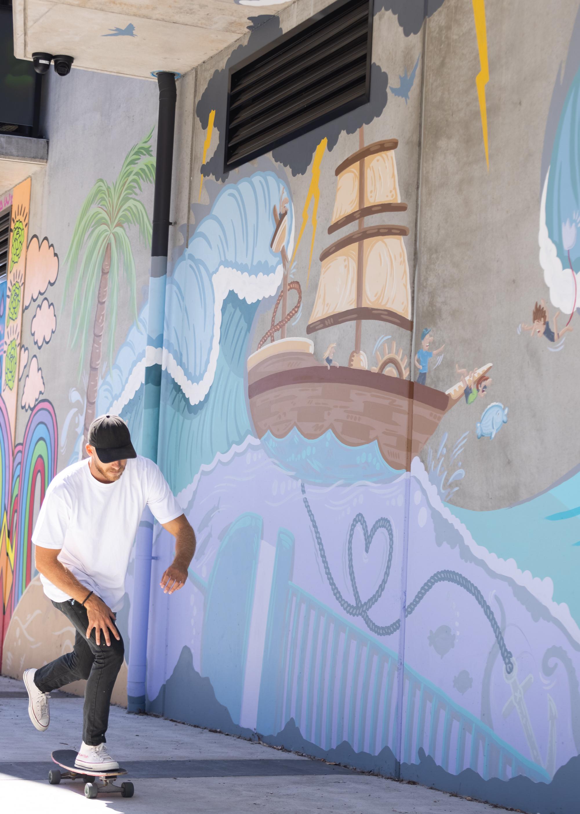 Mitch skates past a mural.