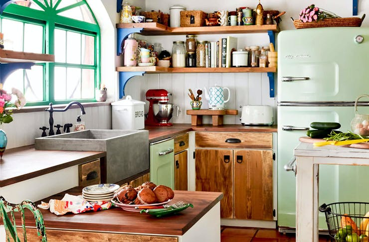 A gorgeous kitchen with vibrant pops of colour, greenery and stacked wooden shelving.