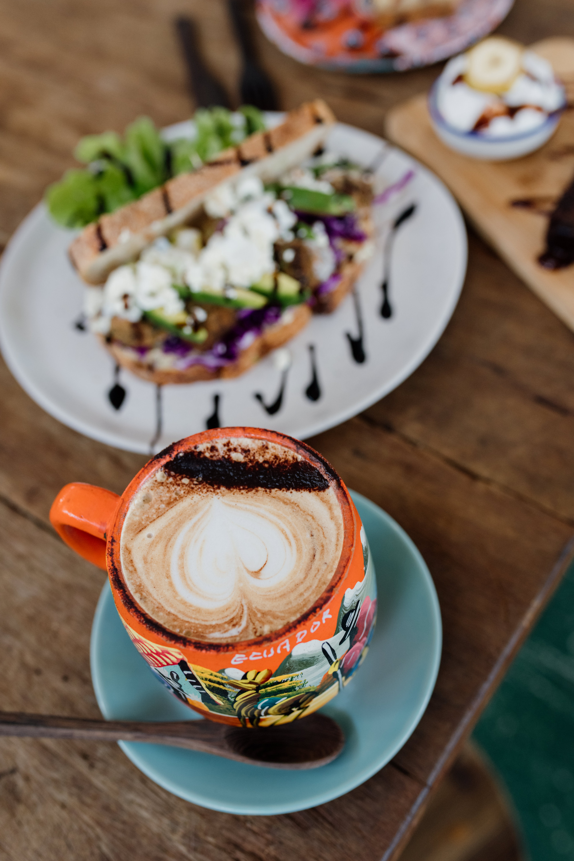 a coffee cup and a smashed avocado dish