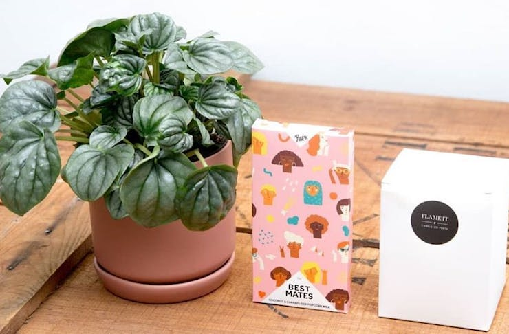 Small pink pot plant, chocolate and candle on a wooden bench