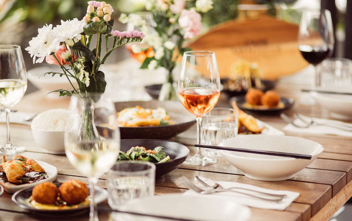 a dining table topped with pretty flowers and share food from Sweetwater