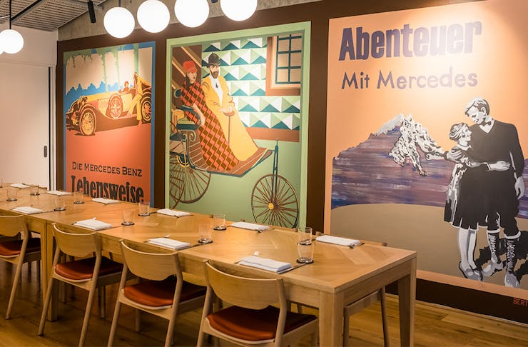 colourful retro artworks on a wall next to a long table