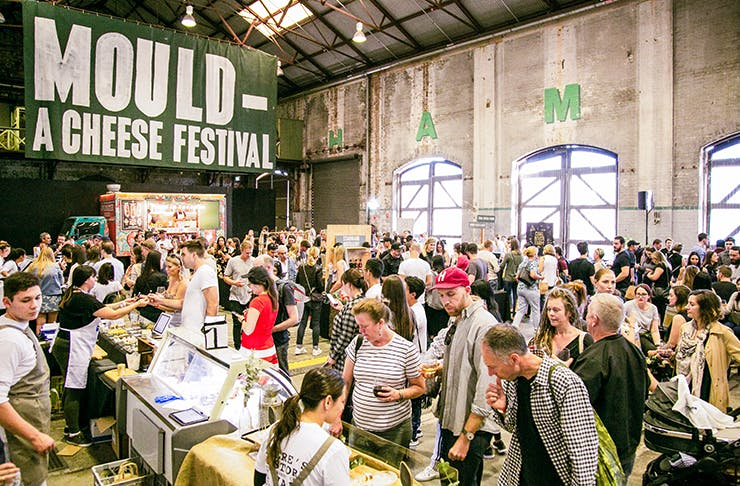 The inside of the cheese festival with people tasting cheese and a green banner that reads Mould Cheese Festival