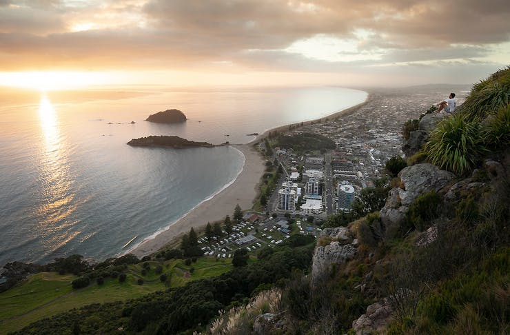 A person sits on Mount Maunganui overlooking the sea, best day walks Tauranga and surrounds
