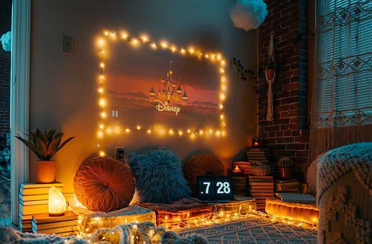 An at home-cinema with projected screen surrounded by fairy lights and cushions