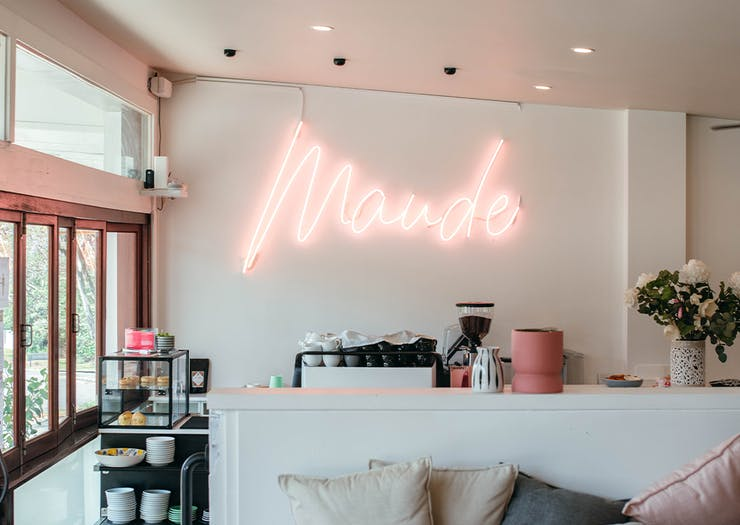 coffee counter at maude with a neon name sign