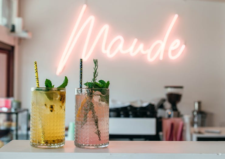 two coloured drinks on a bench in front of a neon sign saying 'maude'