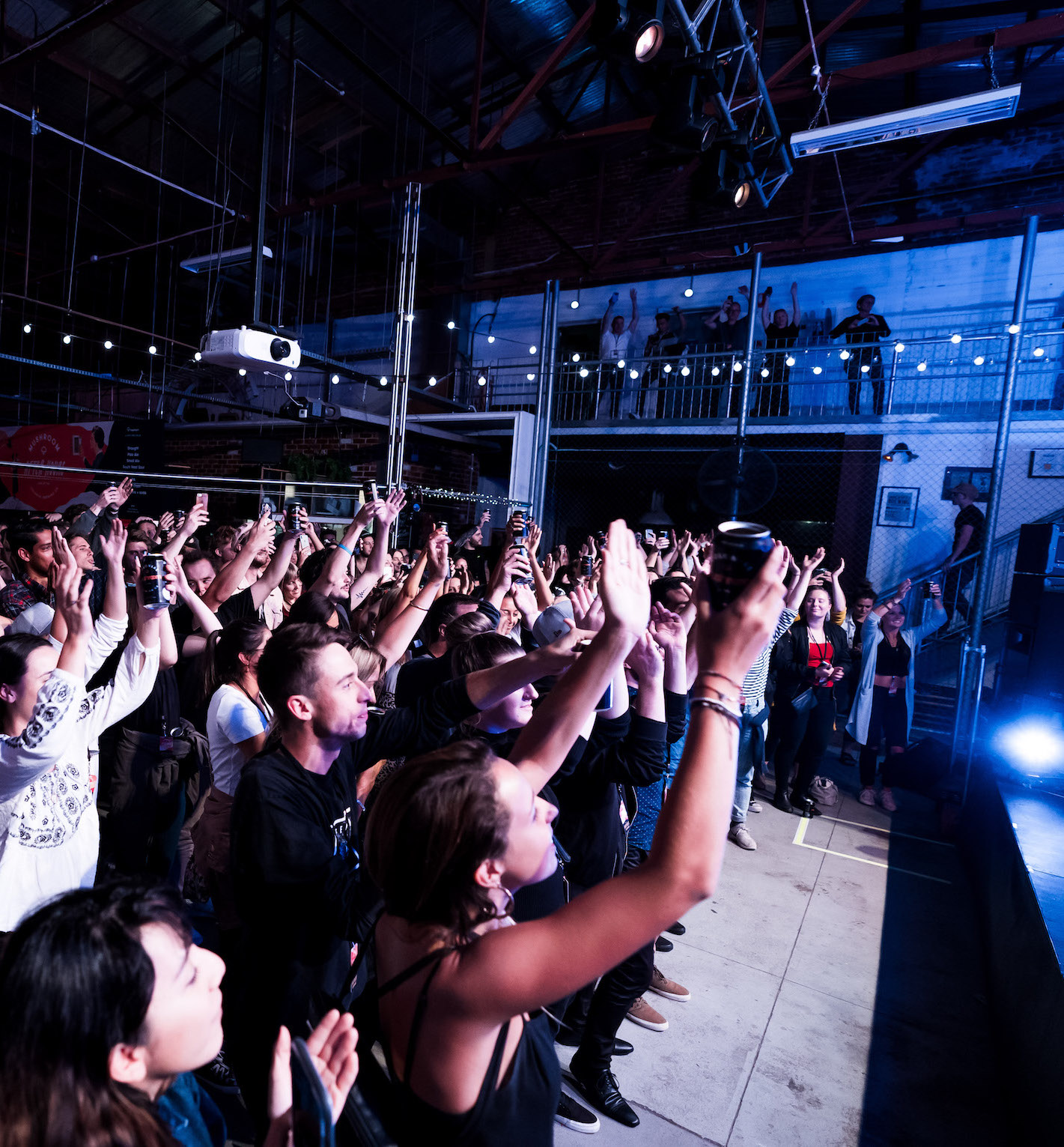 Party goers stand in the crowd with their arms in the air.