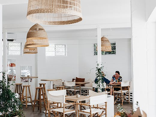 a beautiful white cafe interior with rattan hanging lamps