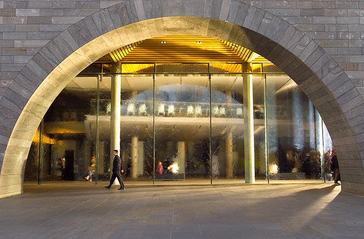 The archway of the NGV with a man walking past.