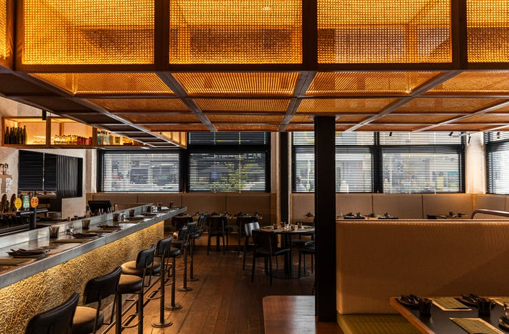 The interior of New Quarter with no diners, a concrete bar and floor and a wicker shelving feature thats lit up.