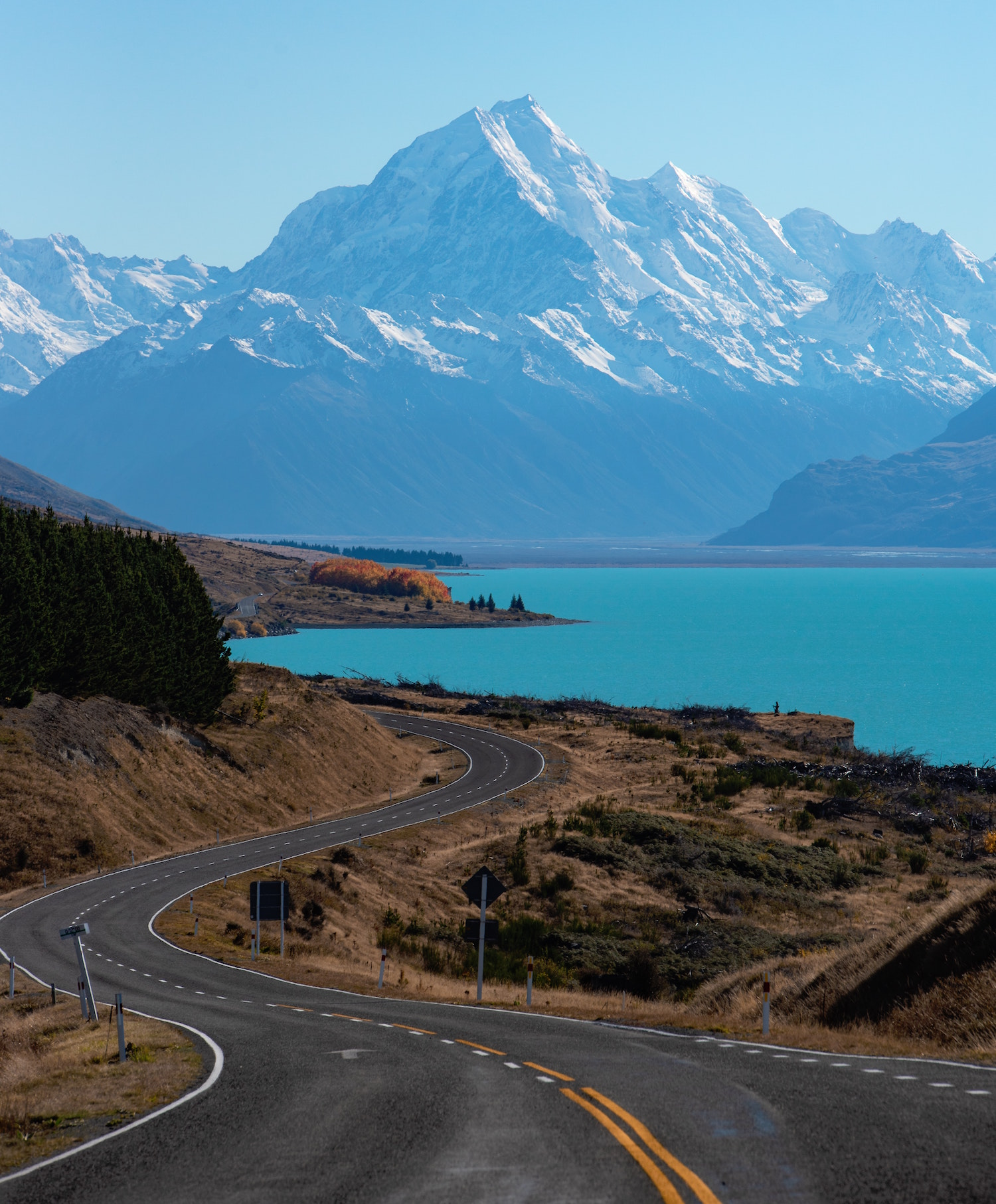 A road snakes it way down to Lake Pukaki with snowcapped mountains in the distance.