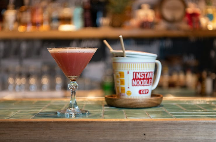a cocktail and a cup of noodles