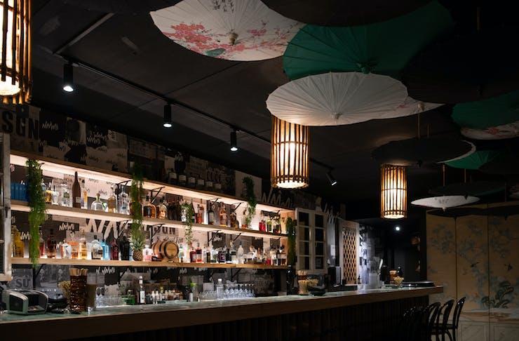 the dark interior of a speakeasy with hanging umbrellas
