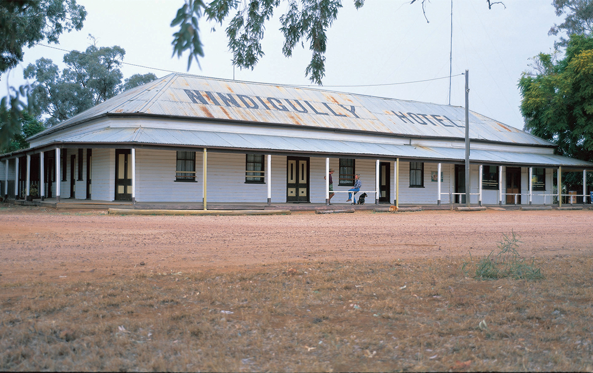 The exterior of Nindigully Pub, with a dirt yard and corrugated iron roof.
