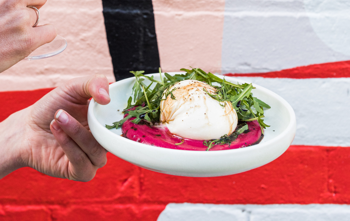 A plate of burrata on a bed of beetroot dip