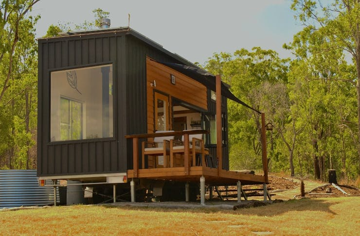 Tiny home with large window and front deck, in bushland.