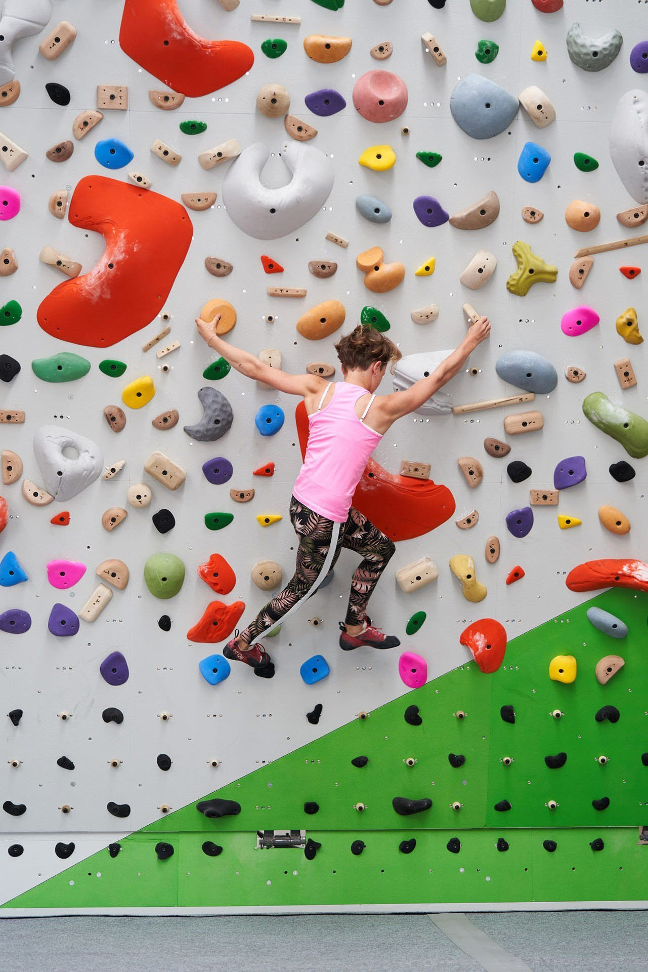 Picture of a girl climbing a colorful bouldering wall
