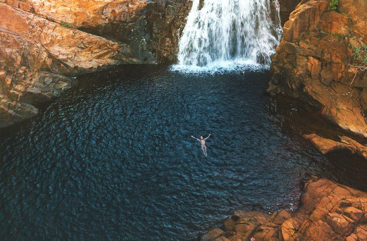 A woman floating in a waterhole at  Edith Falls