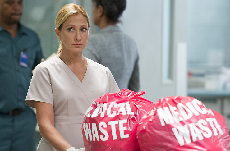Edie Falco as Nurse Jackie looking suspicious as she disposes medical waste