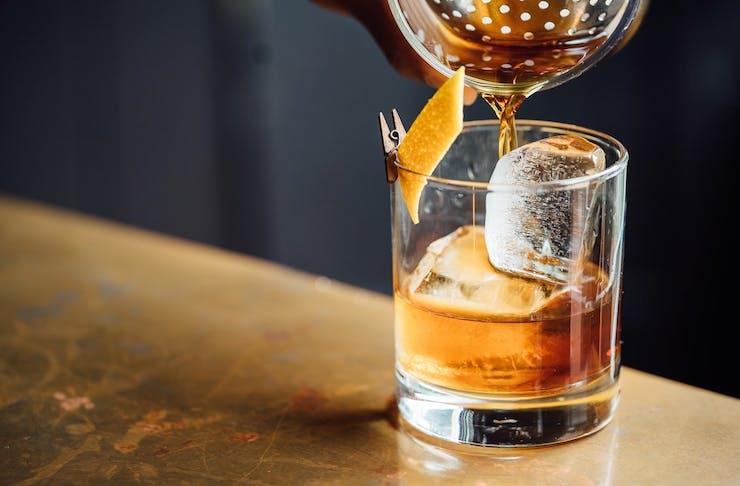 An old fashioned being poured into a short glass