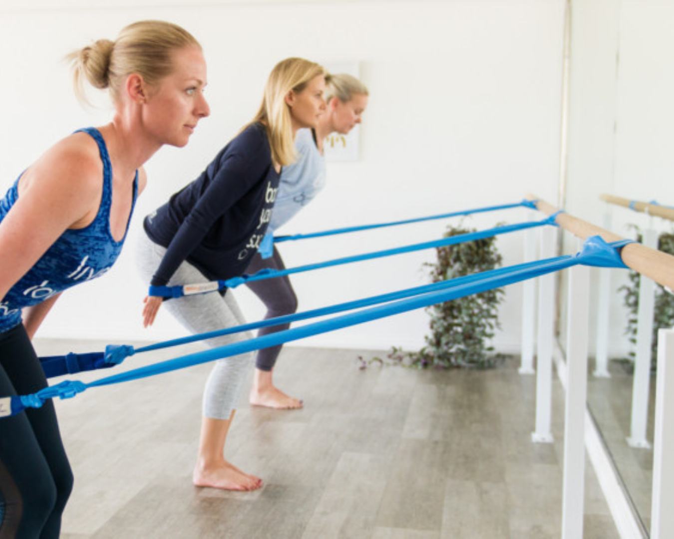3 women practicing barre with resistance bands