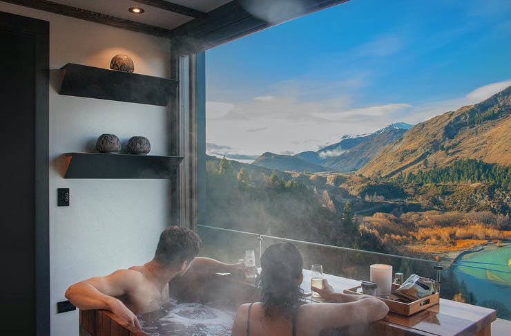 Two people look over the scenery at Onsen Hot Pools in Queenstown.