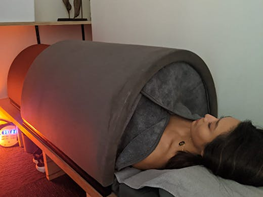 The infrared sauna bed with a woman lying inside it.
