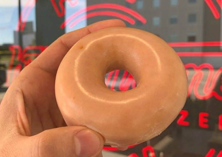 Original Glazed Doughnut held in front of sign