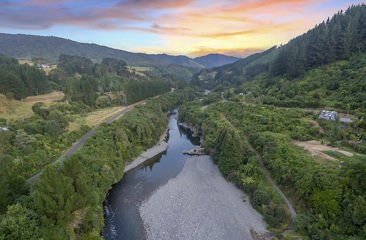 A view over the Otaki gorge with a brilliant coloured sky and green and verdant land all around.