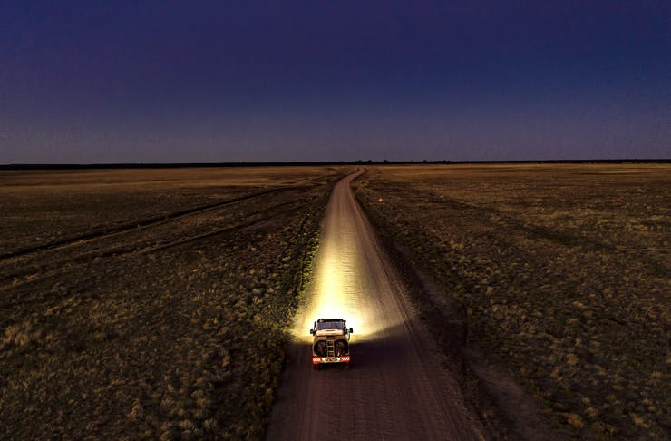 A car drives on a dusty desert road beneath a canopy of stars.