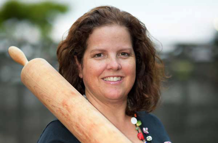 Danielle Butler owner of The Pie Piper and door nuts stands smiling with a rolling pin in her hand