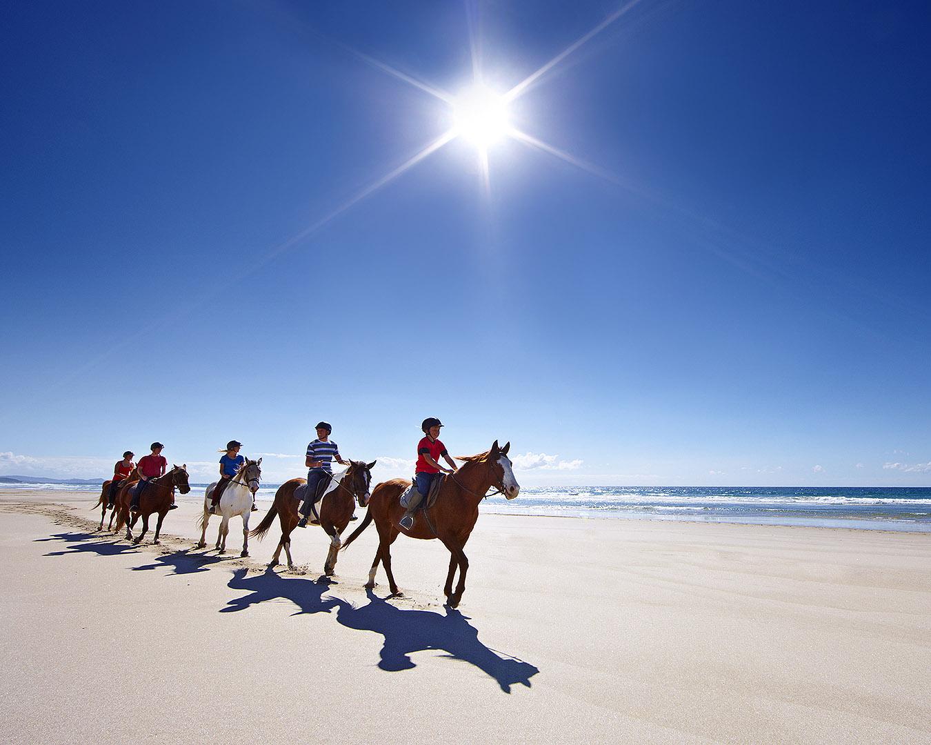 People ride on horseback on Pakiri beach.