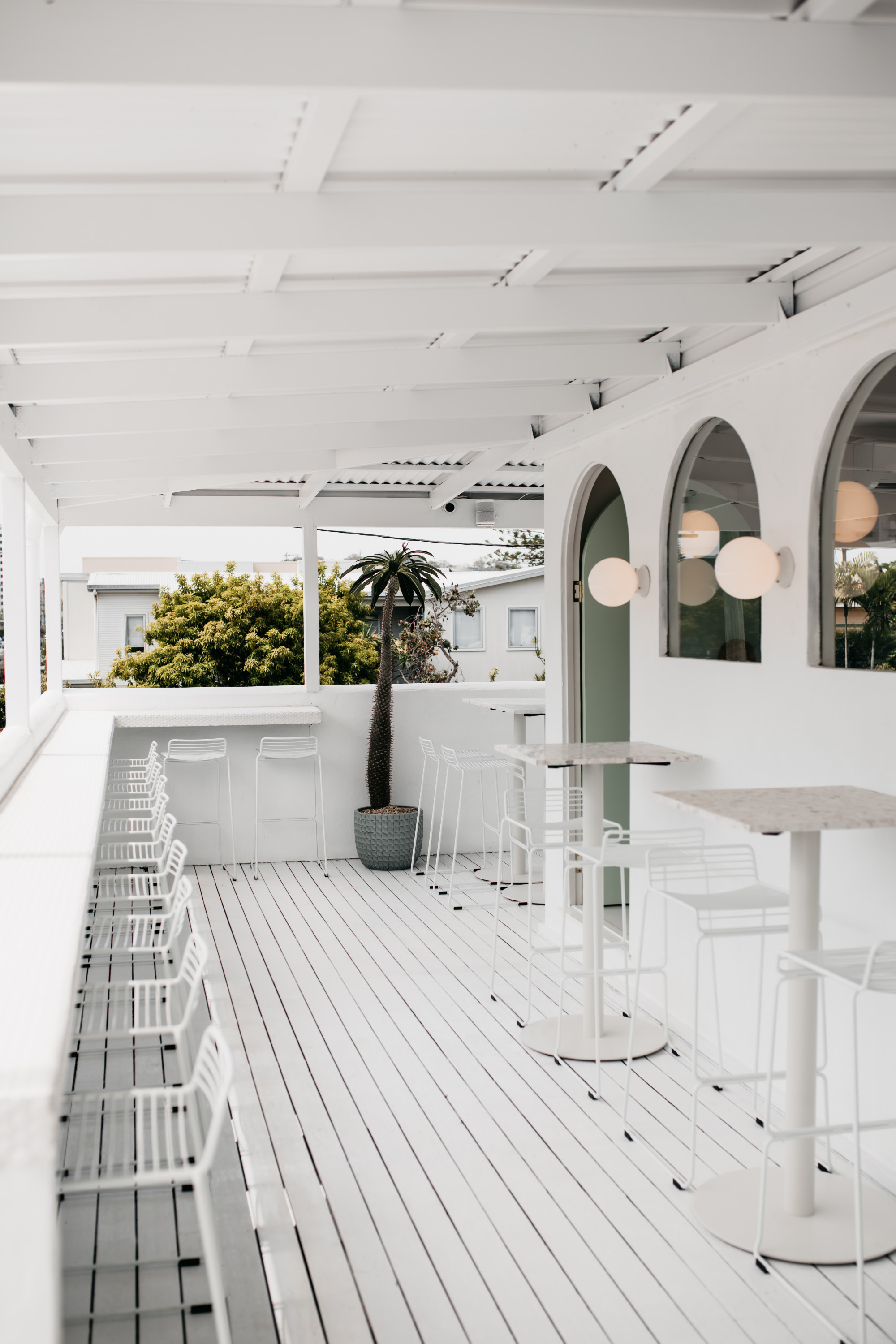 The whitewashed deck and arch windows of Burleigh's Palm Springs cafe.