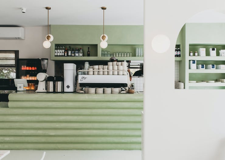 An interior shot of the mint green coffee counter and hanging lights with exposed bulbs at Palm Springs Burleigh.