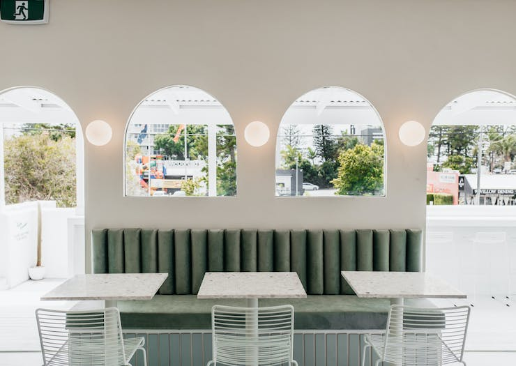 A sage green velvet bench behind a row of arch-style windows against a white wall.