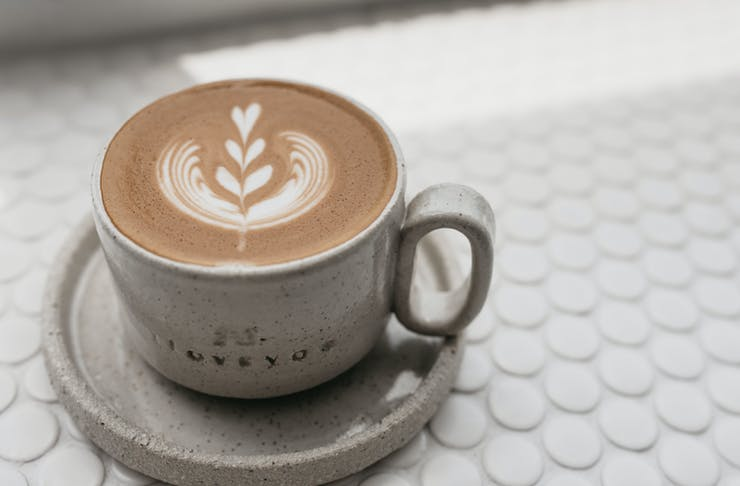 A close-up shot of a latte on a honeycomb tiled counter.
