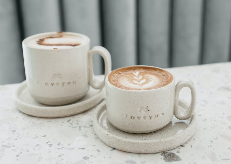 A close up shots of two cups filled with coffee.