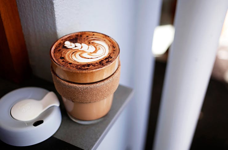 A KeepCup on a bench with the lid off, filled with a latte.