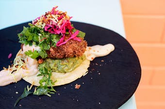 A taco sitting flat topped with guacamole, fried chicken and pickles