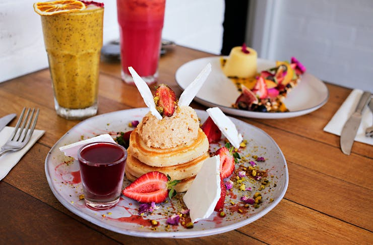 A stack of Perth's best pancakes on a table with smoothies