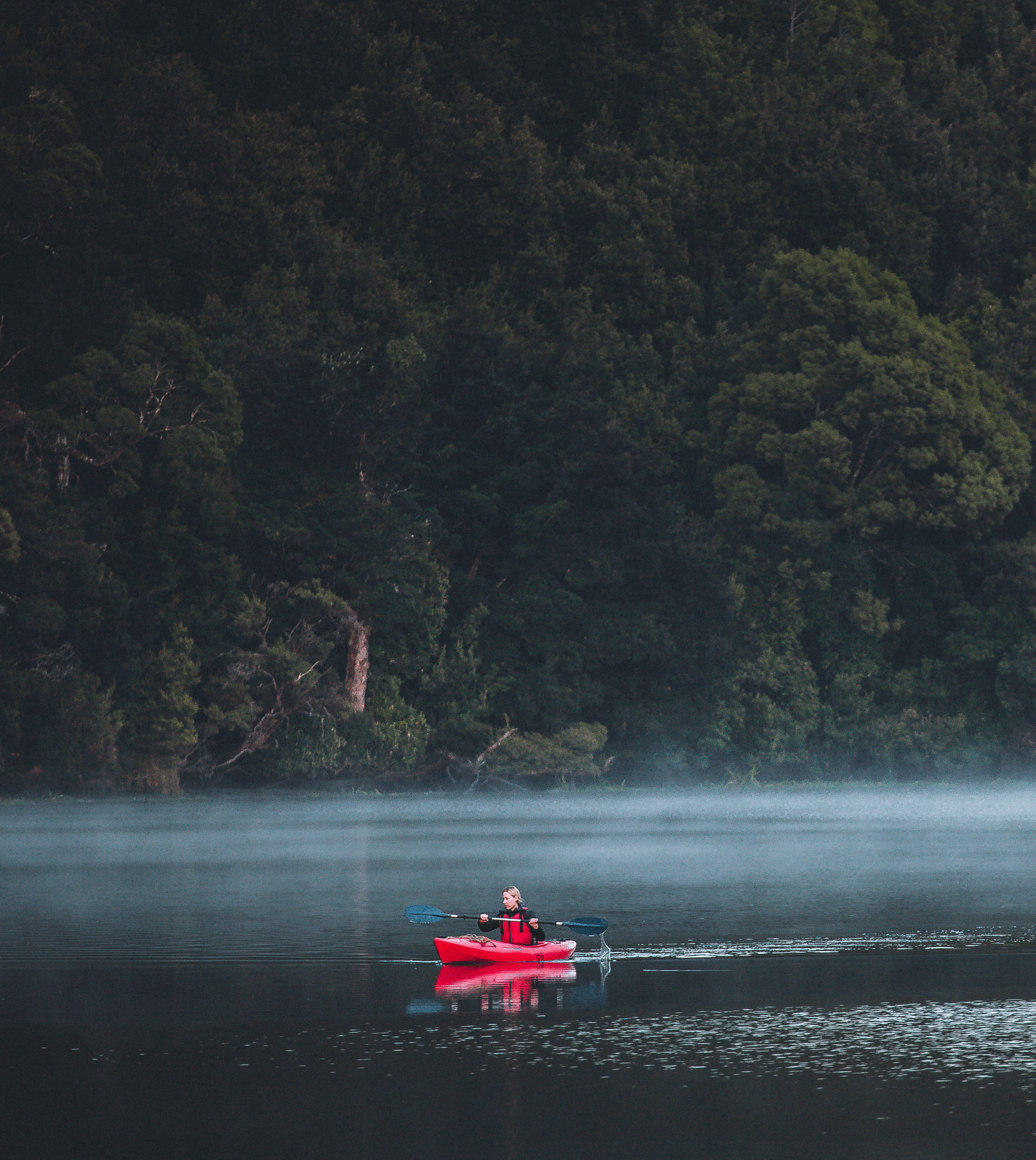 A red kayak floats down the Pieman River in Tasmania.