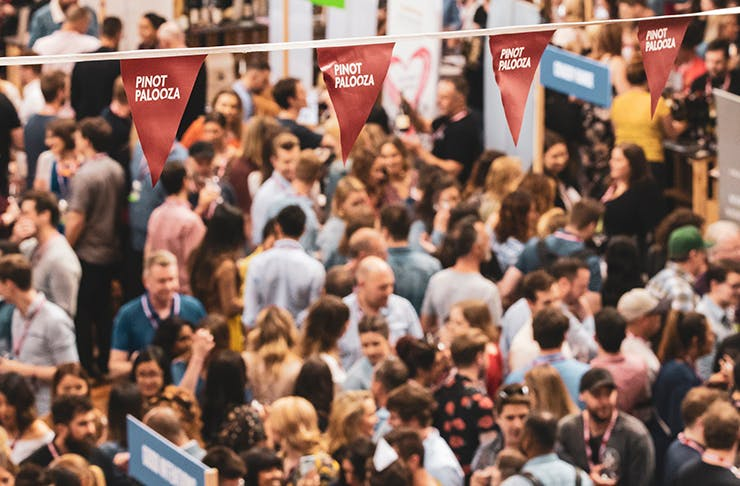 a crowd of people at the pinot event under a red 'pinot palooza' banner