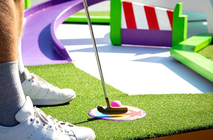 A person in white sneakers playing putt putt golf at Pixar Putt in Sydney.