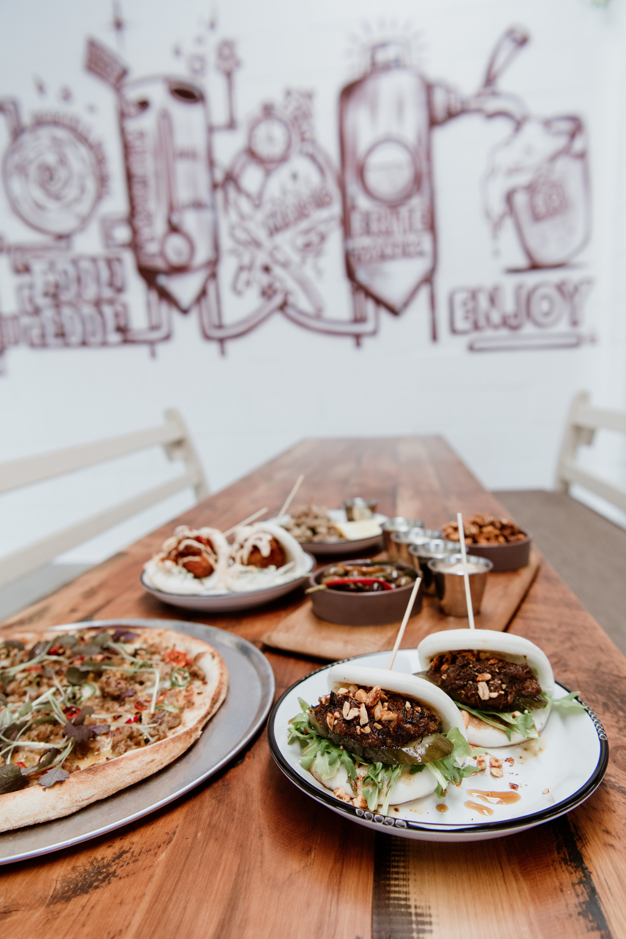 several dishes on a wooden table behind a mural