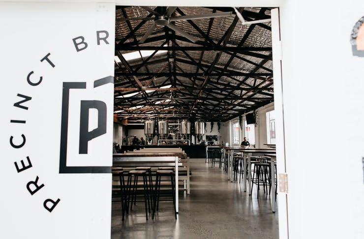 the white doors of precinct brewing half, ajar, displaying the industrial interior of a brewpub