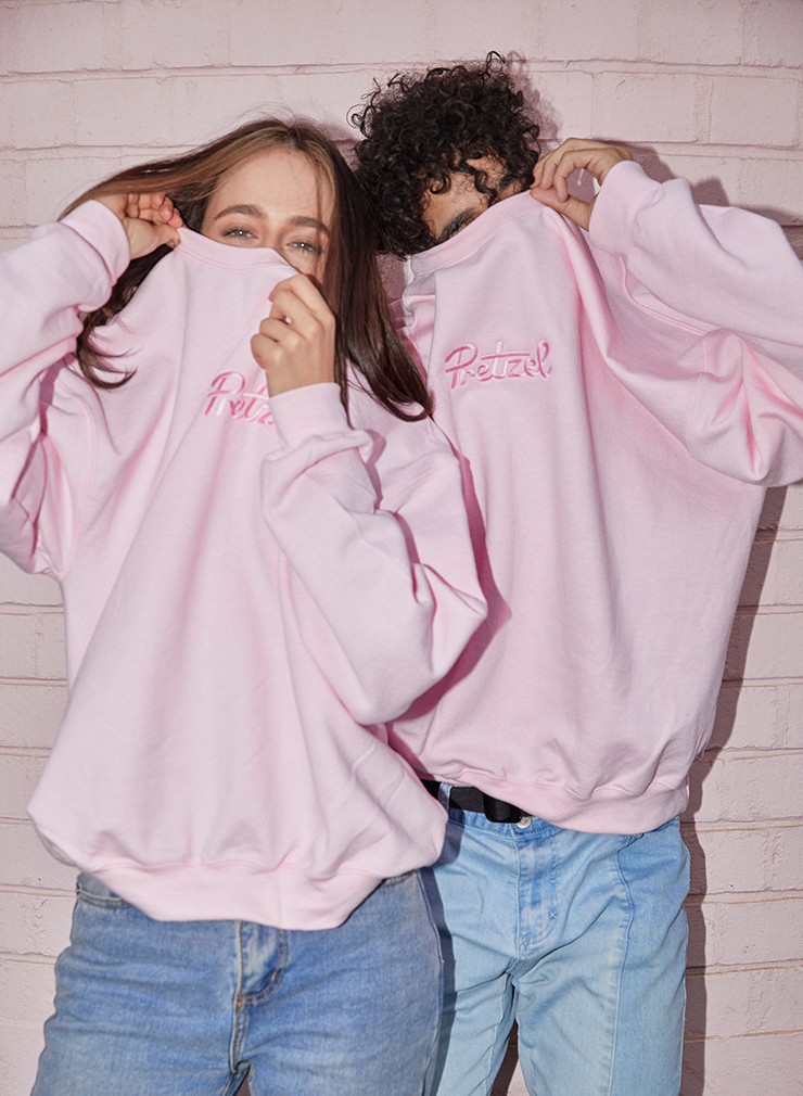 Two people in oversized pink jumpers with the word